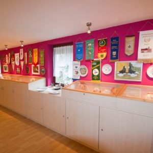 Eine Wand und Vitriene mit Teller und Ehrenbänder